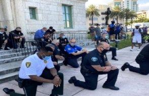 Polis protestocular önünde diz çöktü